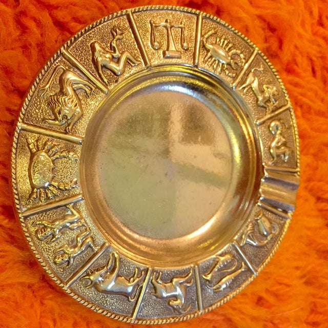Set of 4 mid-century brass ashtrays adorned with zodiac astrological signs around the rims. Brass patina consistent with age.