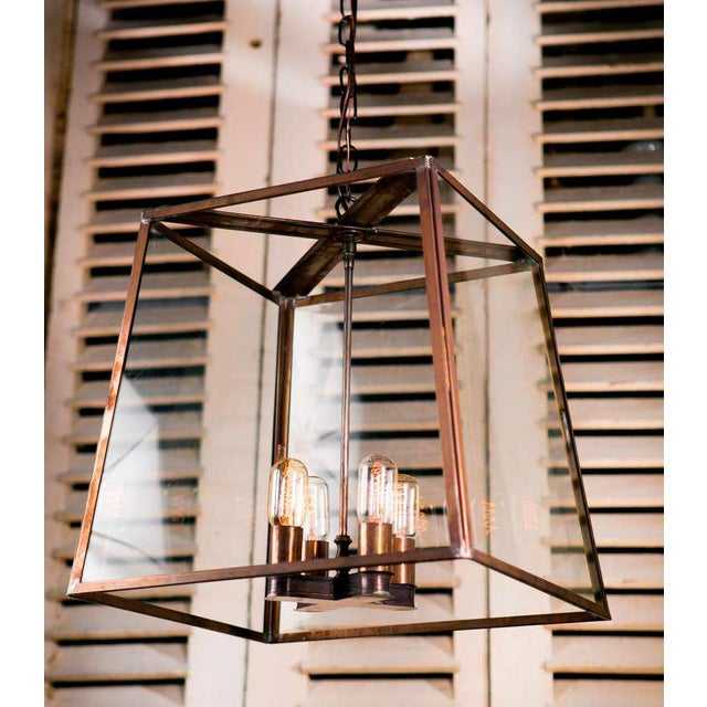 Large darkened brass and glass lantern of a simple and elegant design. Made by hand in the USA, newly wired with 4 Edison...