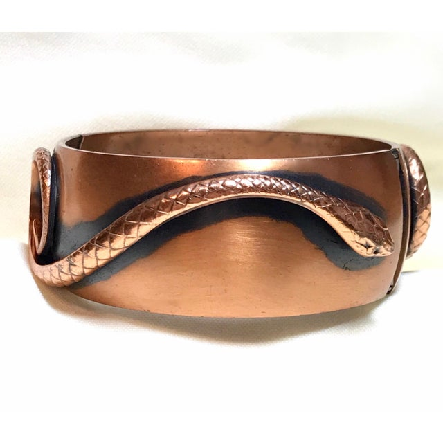 C1950/1960s Whiting & Davis copper hinged bangle embellished with two coiled snakes. The interior circumference of the...