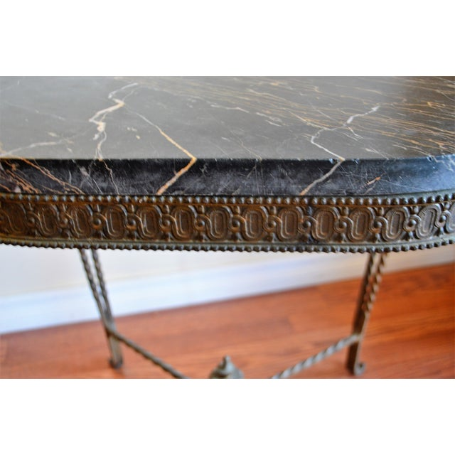 Wrought iron oval side table having double twisted legs, lower cross bar and finial. Attractive etched apron supporting a...