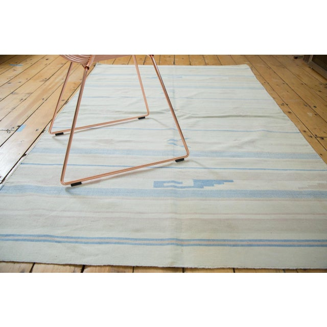 Minimalist Dhurrie rug with striped pattern and southwest inspired aesthetic. Soft earth tones with geometric stylization....