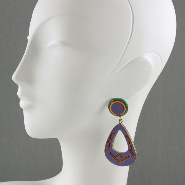 Lovely oversized Lucite earrings for pierced ears. Dangling chandelier shape with lamination and carved tribal motifs....