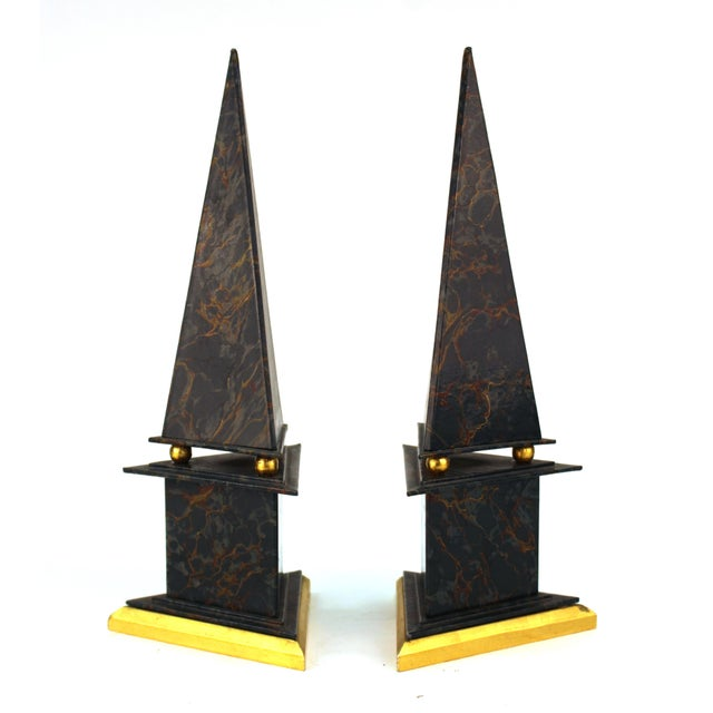 Pair of neoclassical Revival style obelisks made of cardboard with marbled paper and gold foil accents. Each obelisk is...