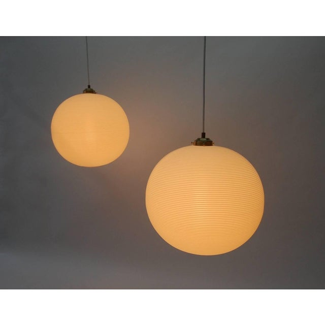 Pair of Rotoflex pendant lights by Heifetz. Constructed of spun striated plastic in contrasting bands of white and off-...