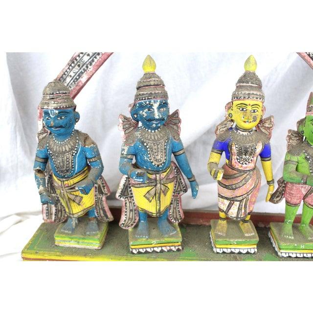 Antique and unique Thai shrine of four colorful figures on a wooden pedestal.