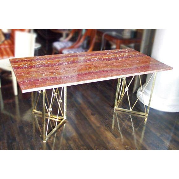 Rare red onyx desk with a polished brass base. The onyx top is an incredible piece of natural stone, featuring highlights...
