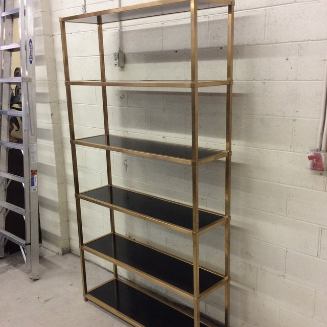 Benton collection Tubular steel frame in patinated brass finish Five wood shelves in high sheen gloss black finish - some...