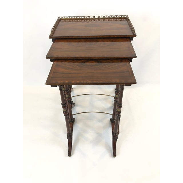 A beautifully designed set of 3 nesting tables of magnificently grained zebra wood having brass gallery on the largest...