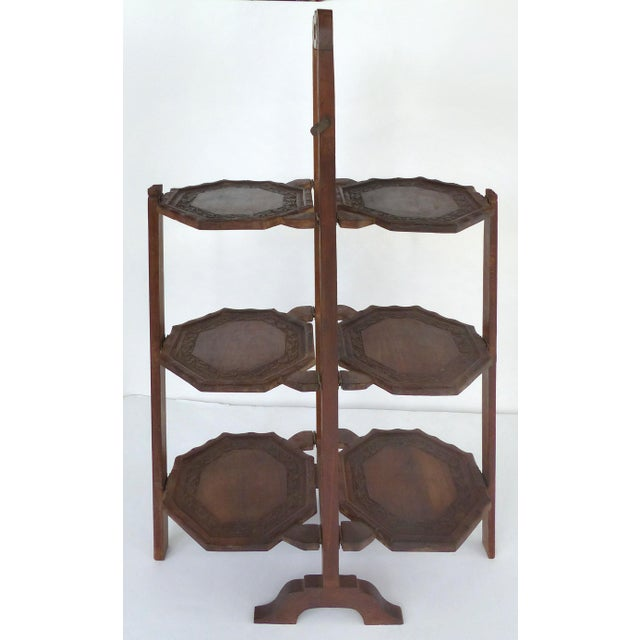 Offered for sale is an antique carved wood 3 tier server stand which fold on both sides. The stand has a carry handle. The...