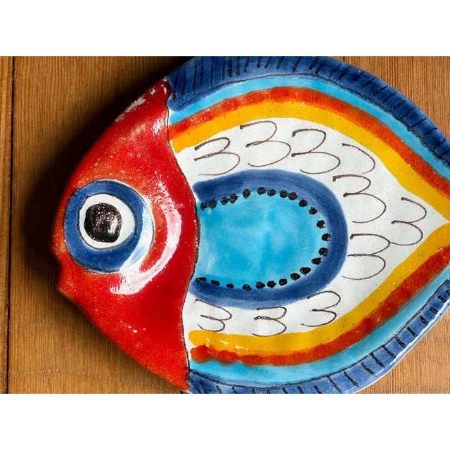 """Sweet little painted fish plate signed DeSimone Italy 88/2. Very vibrant colorful colors. Measures 9""""long x 7"""" wide. Good..."""