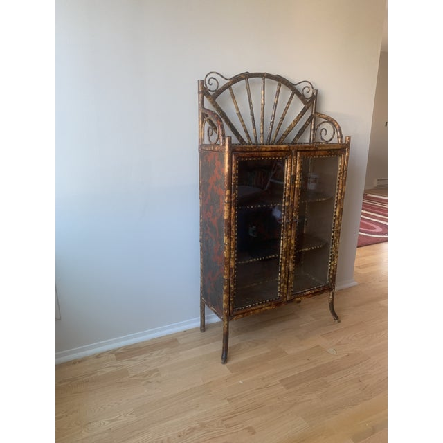 Lovely antique (ca. 19th century) burnt bamboo etagere with glass doors. The faux tortoiseshell pattern is complemented by...