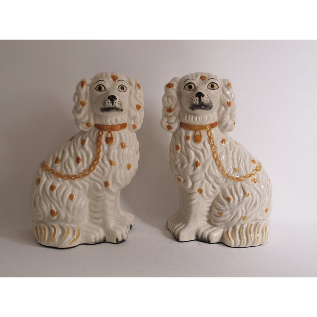 Pair of hand-printed Staffordshire style ceramic dogs portraying a pair of spaniels. Foam pads on the bottom to protect...