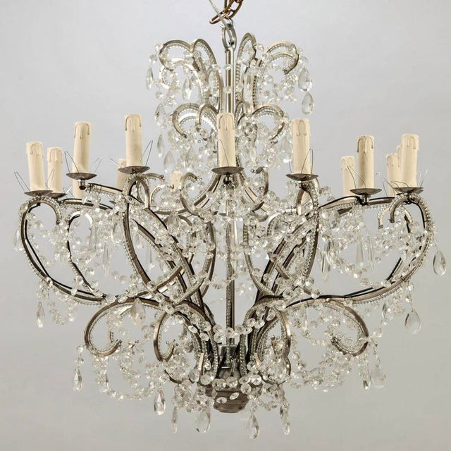 Large beautiful 1950s French sixteen light chandelier featuring silver tone metal frame, sixteen arms lined with clear...