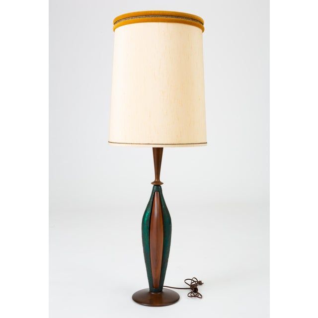 A pair of tall table lamps by the Los Angeles-based Moderna Lamp Manufacturing Co. The lamps have a round base in dark...