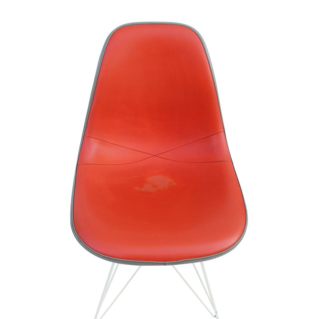 Pair of vintage Herman Miller Eames fiberglass side shell chairs. One is upholstered in orange, the other in magenta Both...