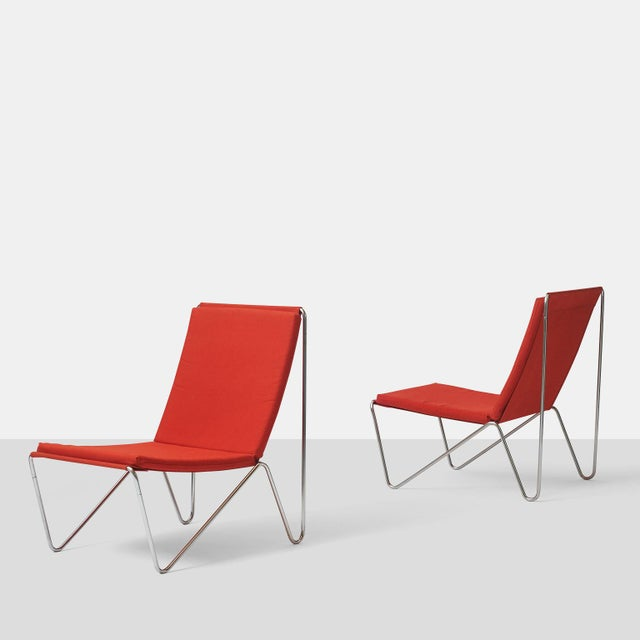 """A pair of """"Bachelor"""" chairs by Verner Panton for Fritz Hansen. Tubular steel frames support red canvas slings, upon which..."""