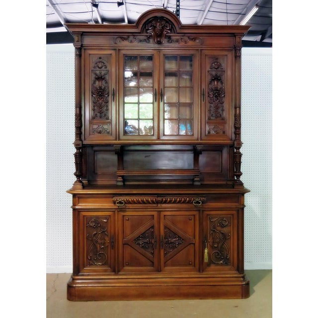 This is an antique Renaissance style 2-piece china cabinet. The top has 4 doors containing 2 shelves. The bottom has 2...