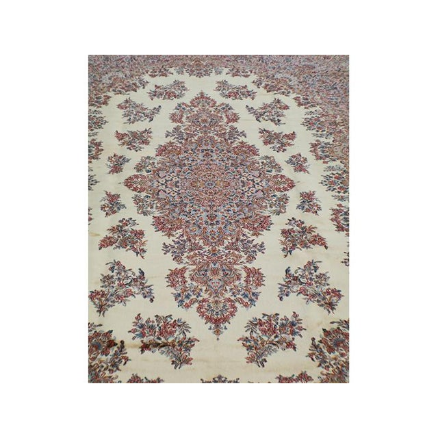 Classic Kerman design with floral pattern all over. This is a wool rug. Oversized. The background color is ivory, and the...