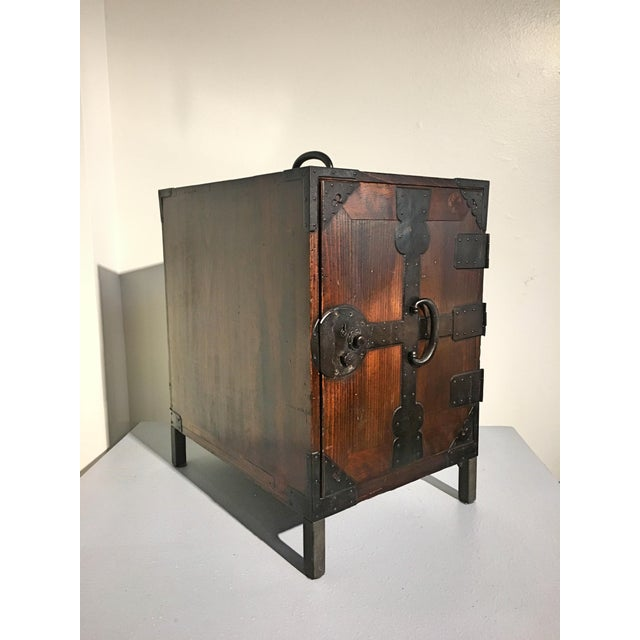 A beautiful Japanese Meiji Period elm and cypress ship's chest, called a fune tansu, mounted with iron fittings. Made for...