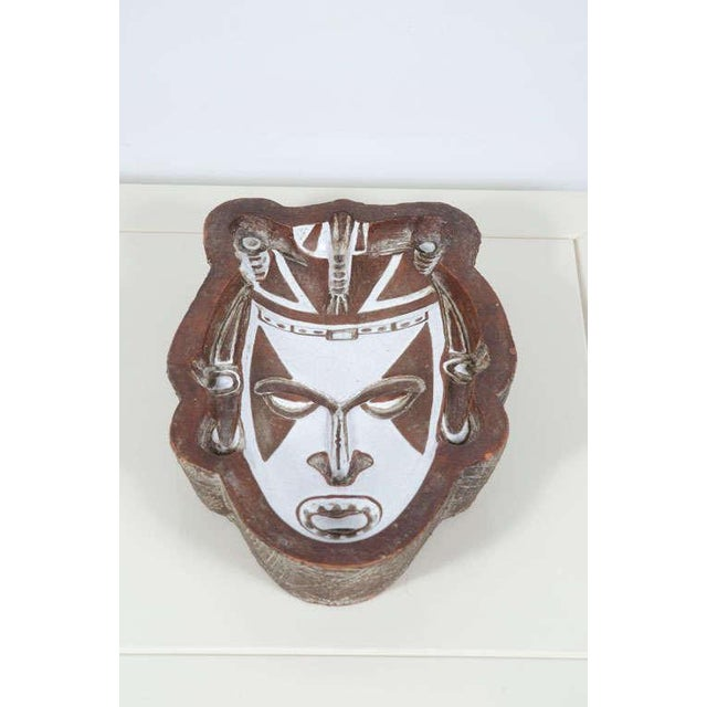 A figural ceramic mask dish comprising a tooled edge, an impressed tribal design in white crackle glaze on a matte brown...