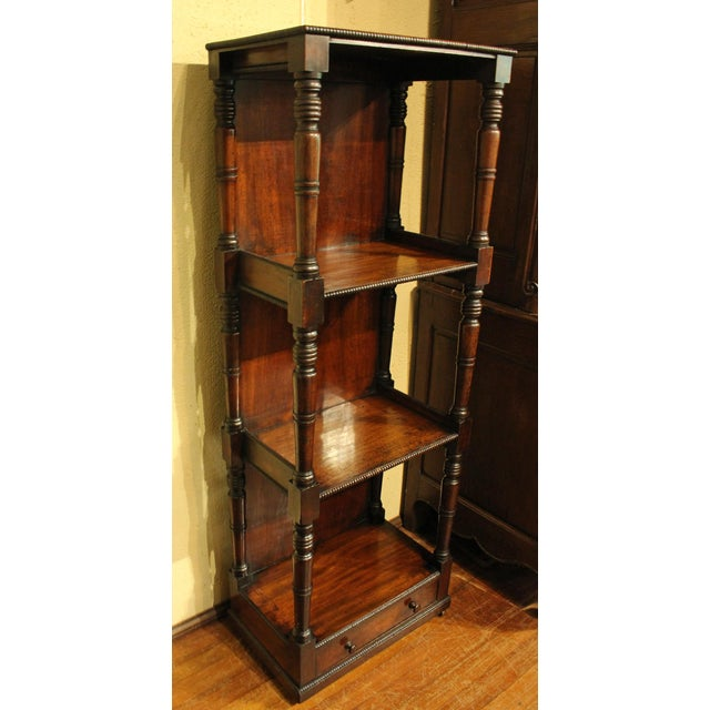 A William IV What-Not-Stand or narrow bookcase. English, c. 1830. Mahogany. Four tiers; well turned, tapered uprights....