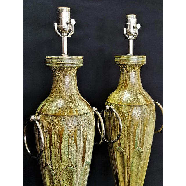 Offering a large and sophisticated pair of gold and light green ceramic table lamps, circa 1950s. These lamps are...