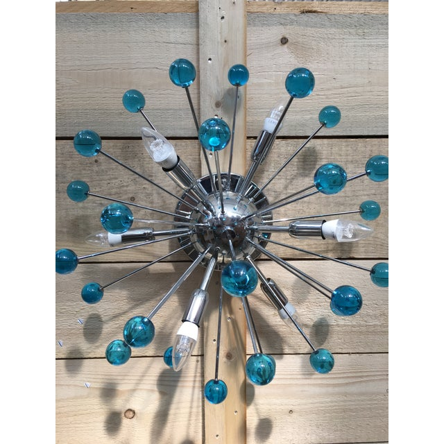 Flush-mount or Wall sconce with a chrome base and round Murano glass in a light sea blue color. The fixture is in the...