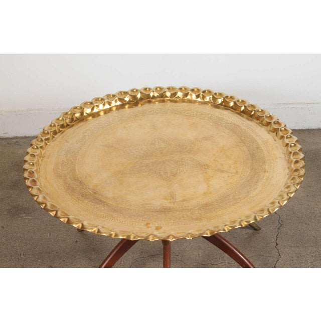 Large round Moroccan brass tray table 36in. Polished brass tray, very good condition, standing on folding mahogany base...