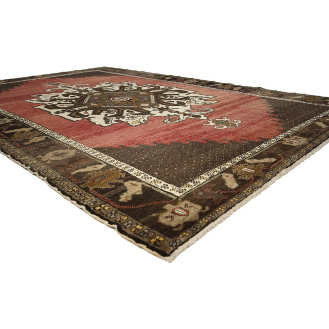 This hand-knotted wool vintage Turkish Oushak area rug features a large medallion in creamy-beige with contrasting...