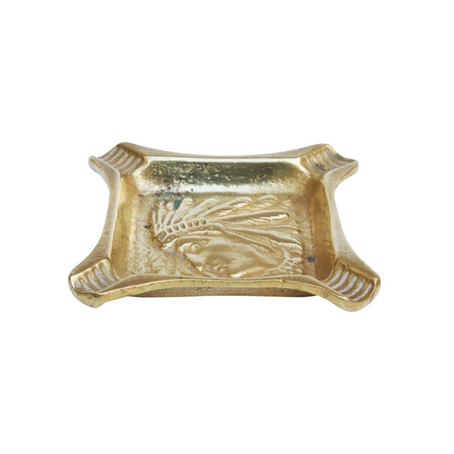 A solid brass square ashtray. The center is decorated with the profile of a Native American Indian warrior wearing a halo...