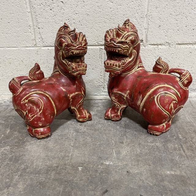 Great pair of carved wood foo dogs in that orangey red color everyone is so hot for these days. I do not know the age....