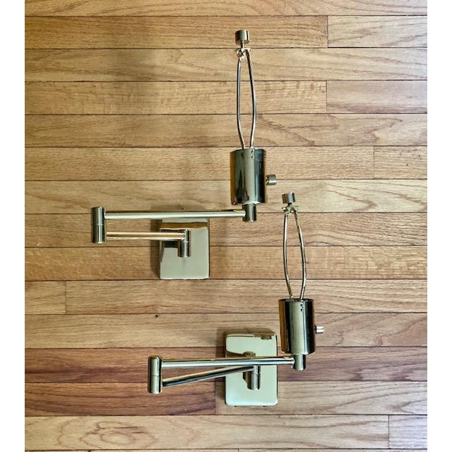 A pair of original brass swing arm lamps designed by George Hansen in late 1960s, and manufactured in the 1970s by...