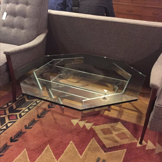A striking coffee table in stacked chrome bars and octagonal glass top.