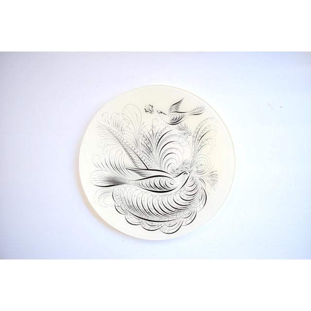 A decoupage glass plate in the style of John Derian, in white and black, with calligraphic birds and a butterfly...