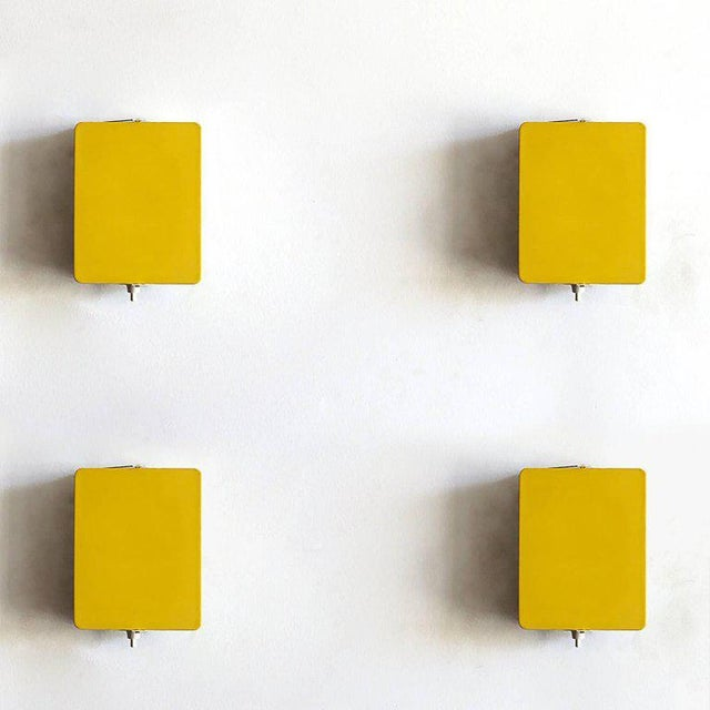 Iconic enameled wall lights by Charlotte Perriand with adjustable reflectors in rare yellow finish, optional horizontal or...