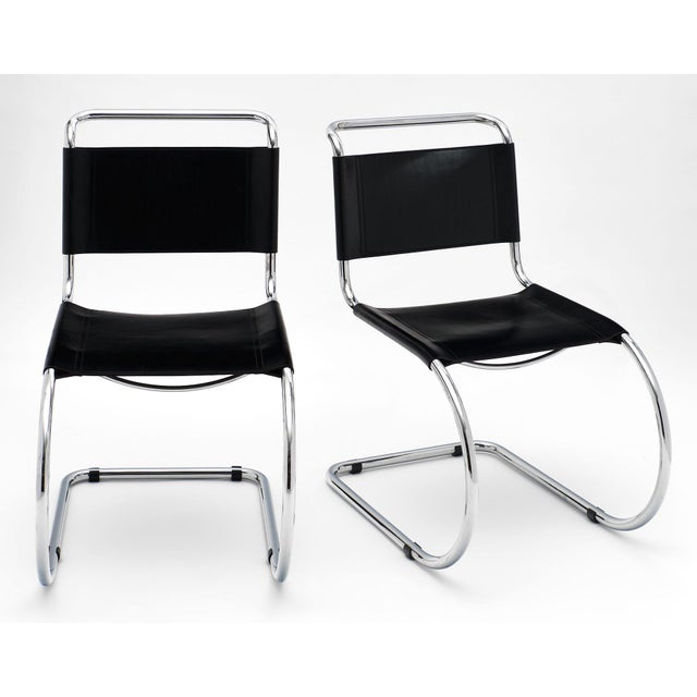 A pair of vintage Mies van der Rohe cantilever chairs with chromed metal structures and black leather seats. We love the...