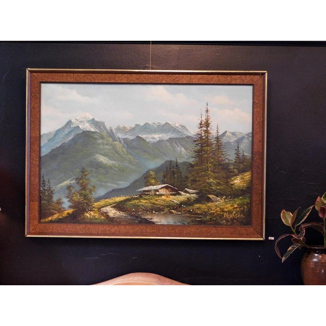 This beautiful framed oil painting features a stunning landscape scene. The frame is made of wood, cork and a brass trim....
