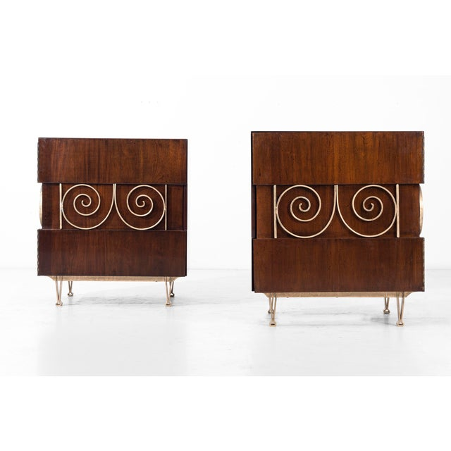 These end tables are covered in brass plated ornamentation, supported by brass V-shaped legs; the wood is mahogany and...
