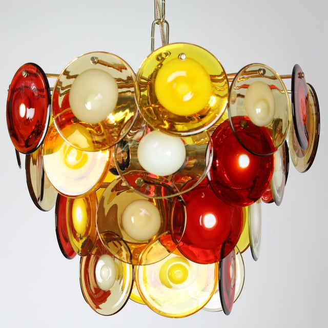 Colorful chandelier featuring 36 round hand-blown glass discs in red, yellow and white glass in a cascading formation....