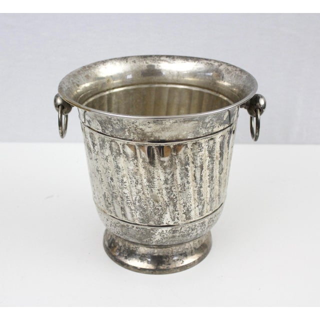 Vintage silver plated open ice bucket or champagne bucket with scoop. Has two handles for carrying. The bucket has no...