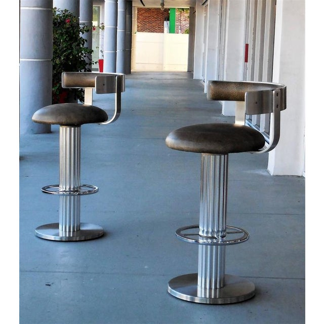 Pair of bar stools by Design for Leisure. The bases are a combination of polished and brushed stainless steel. Wide round...