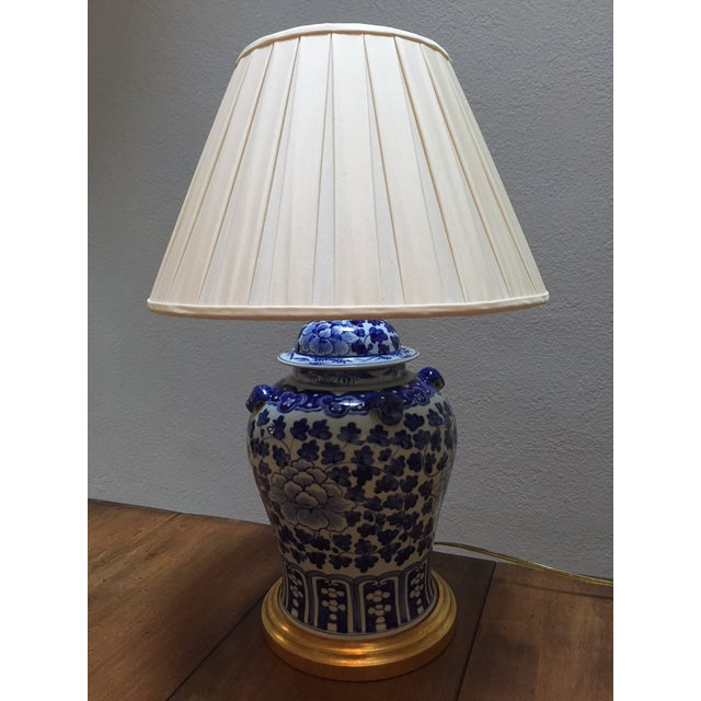 This blue and white porcelain lamp has hand painted flowering vines and flowers. The socket is 60 watts, bulb not...