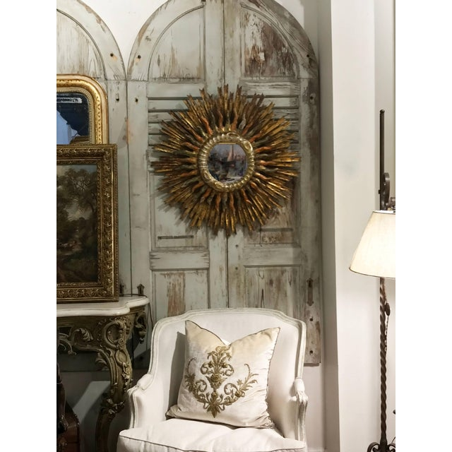 This exquisite Italian painted and gilded double sunburst mirror from the late 19th century features a clear mirror in the...