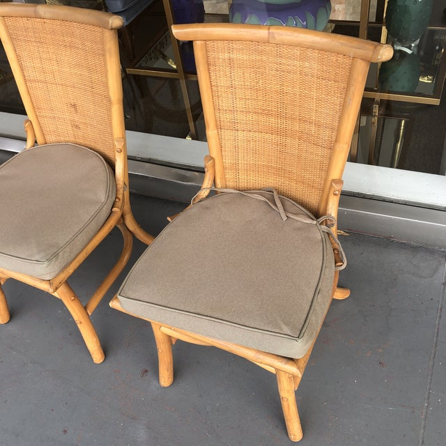 Set of 4 dining chairs with woven rattan pagoda style backs and a faux bamboo curved design. Would look great in an...