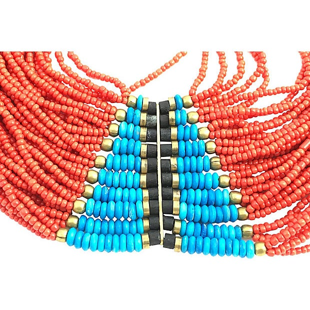 Antique multi-strand statement necklace featuring brass and wood accents placed between plastic turquoise- and coral-hued...