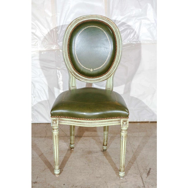 An impressive set of six Louis XVI style dining chairs with original green leather. Leather seats and backs are detailed...