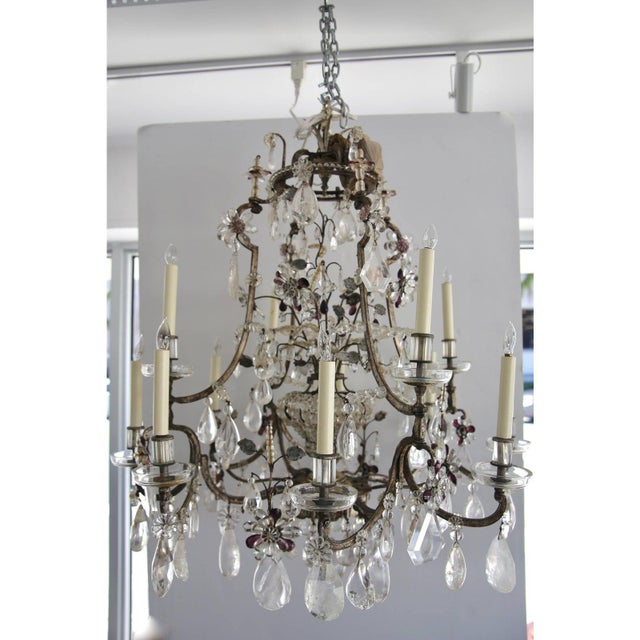 This piece was created by the iconic Maison Baguès and is in the Louis XV style with its 12 lights and silver leafed steel...