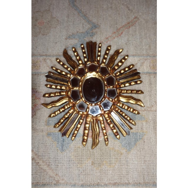 Giltwood sunburst mirror from Italy. 20th century. Would work well within a grouping of paintings or other mirrors....
