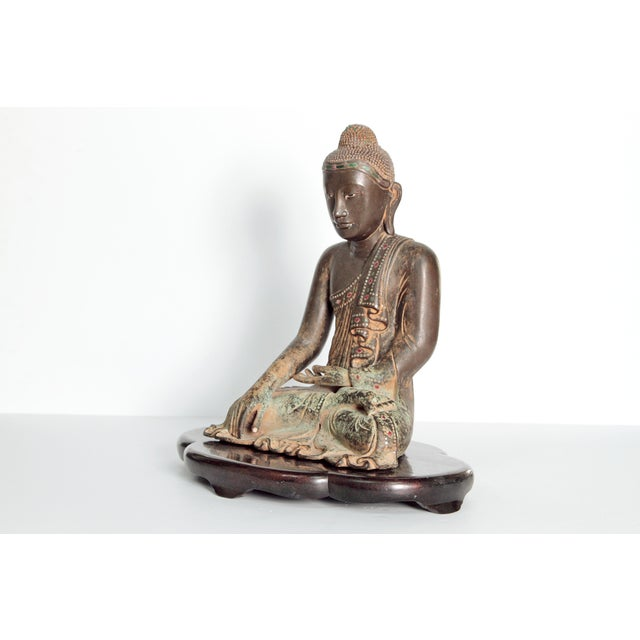 A figure of a 19th century seated Buddha in a meditative pose. Patinated and gilt bronze accented with pieces of colored...