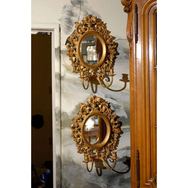 Pair of Italian gilt candle sconces with oval mirrors framed in a beveled frame and surrounded by pierced decorative...